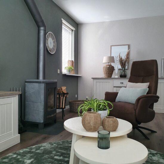 houtkachel groene wand vloerkleed dressoir